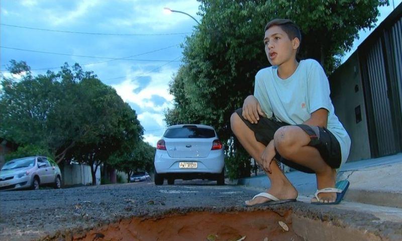 Garoto cai com bicicleta em buraco de rua e perde dois dentes