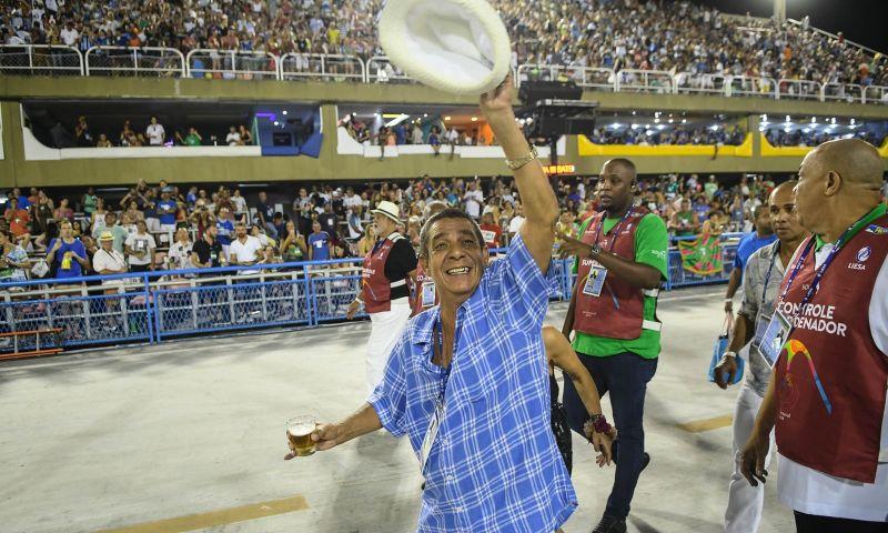 Zeca Pagodinho anda com cerveja na mão e tira foto com garis em desfile da Portela