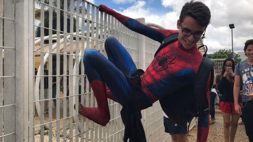 Estudante vai de homem-aranha e escala grade