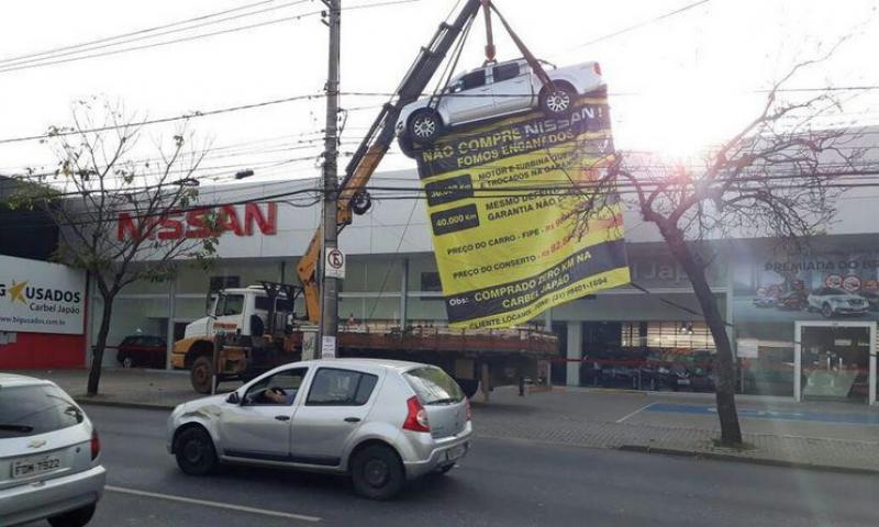 Em protesto, cliente pendura carro em frente a concessionária: 'Fomos enganados!'